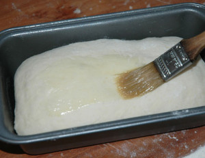 place loaf into butterd pan and brush with butter